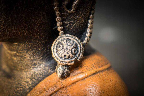 Crowned Buddha praying details earing