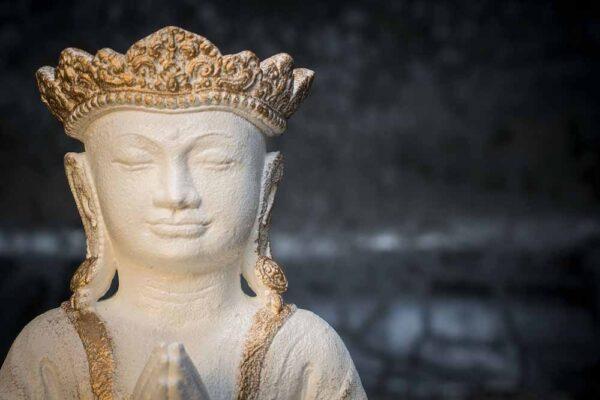 Crowned Buddha praying details white