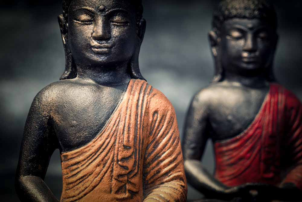 Sitting Buddha folded hands details red orange