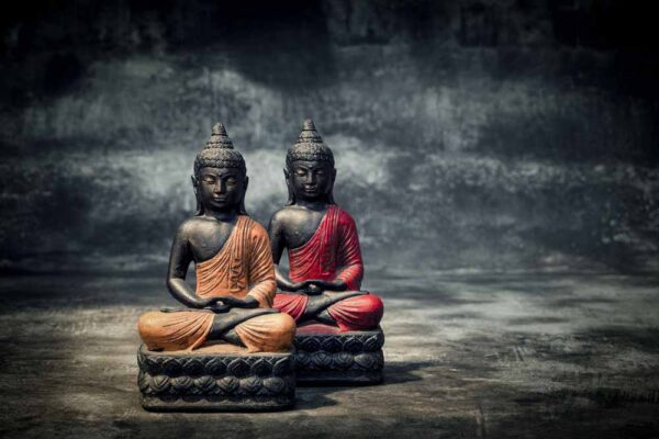 Sitting Buddha folded hands total view orange red