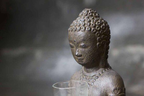 sitting Buddha on base with candle